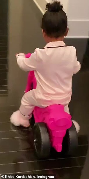 Joy ride: Before sharing a portrait of herself and her mini-me, the proud mom captured video of the adventurous tot riding around her Calabasas mansion on a pink bike