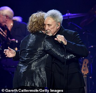 Enjoying themselves: Tom and Mick shared an embrace as they performed together