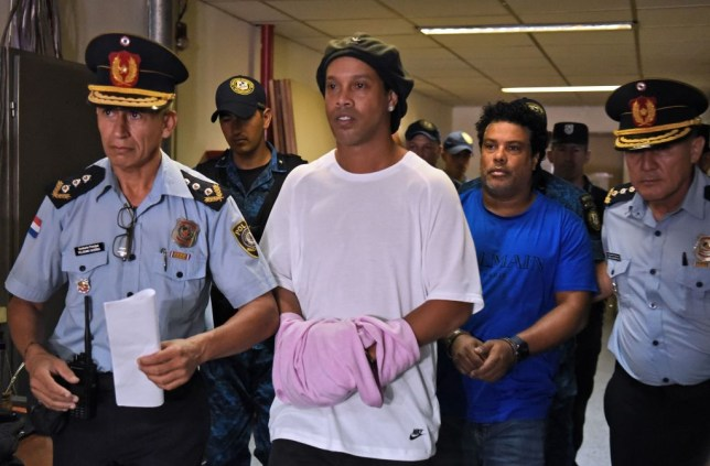 Brazilian retired football player Ronaldinho (C) and his brother Roberto Assis (R) arrive at Asuncion's Justice Palace to appear before a public prosecutor who will decide whether to grant them bail or not following their irregular entry to the country, in Asuncion, on March 7, 2020. - Former Brazilian football star Ronaldinho and his brother have been detained in Paraguay after allegedly using fake passports to enter the South American country, authorities said Wednesday. (Photo by Norberto DUARTE / AFP) (Photo by NORBERTO DUARTE/AFP via Getty Images)