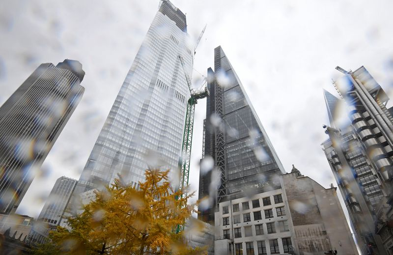 © Reuters. FILE PHOTO:  A tree covered in autumn foliage is seen with office skyscrapers around it during rainfall in the City of London, Britain
