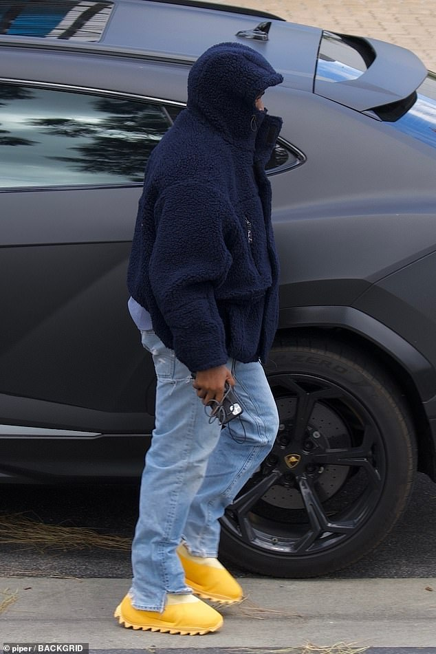 Ultralight Beam: The 42-year-old rapper bundled up in an oversized navy blue polar fleece jacket featuring a hood over a grey T-shirt and relaxed fit light blue jeans