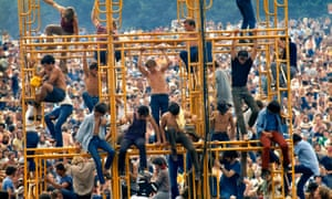 Woodstock festival, New York: August 1969. Crowd and people sitting on the sound tower.