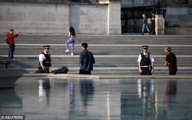 Police Officers enforce the lockdown measures at Central London's Trafalgar Square, asking people to leave the square and abide by the social distancing measures