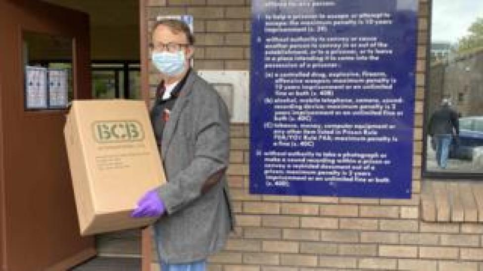 Man wearing mask holding box of hand sanitiser outside Cardiff prison
