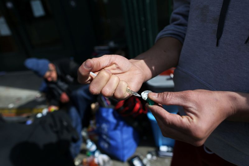 © Reuters. A IV drug user fills a syringe with street drugs in Vancouver's Downtown Eastside.