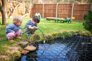 Two small children filling up a pond with a hose