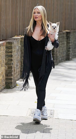 Kind: Caprice cradled her pet pooch in one hand as she strolled through her neighbourhood
