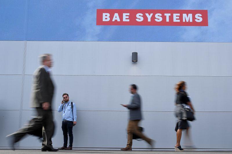 © Reuters. Trade visitors walk past an advertisement for BAE Systems at Farnborough International Airshow in Farnborough, Britain