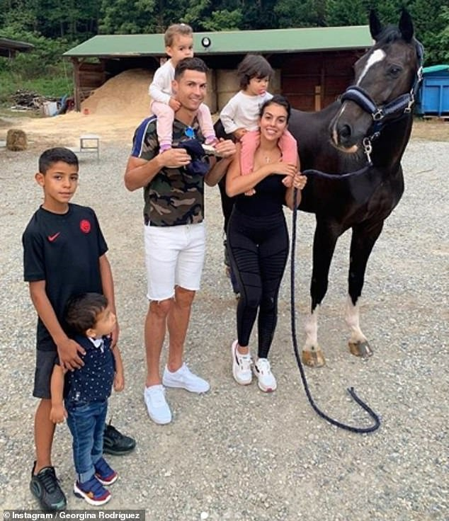 Family first:The football ace and the former shop assistant have been dating since 2016 (pictured with his four children, including Georgina's daughter Alana)