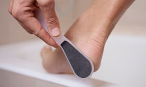 young man using a foot raspcloseup of a young caucasian man in the bathroom using a foot rasp