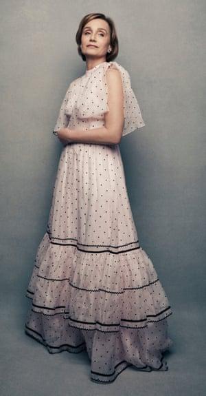 Kristin Scott Thomas standing wearing a pretty pink dress