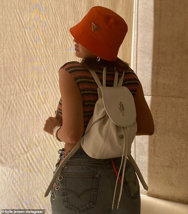 90s girl:The youngest Kardashian-Jenner sibling rocked a retro look with a mini back pack and a bucket hat paired with denim jeans and a striped sleeveless top