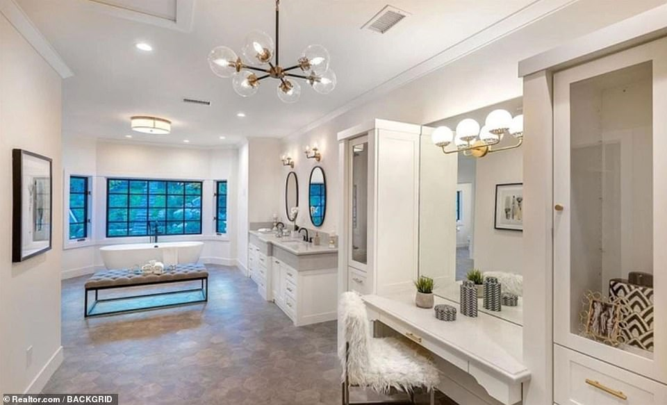 Glitzy: The master bath also has dual vanities and a glam station