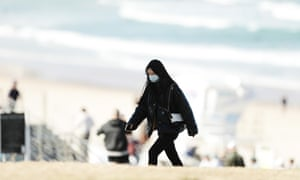 A woman wears a face mask at Bondi Beach in Sydney. People in the city have been strongly encouraged to wear masks.
