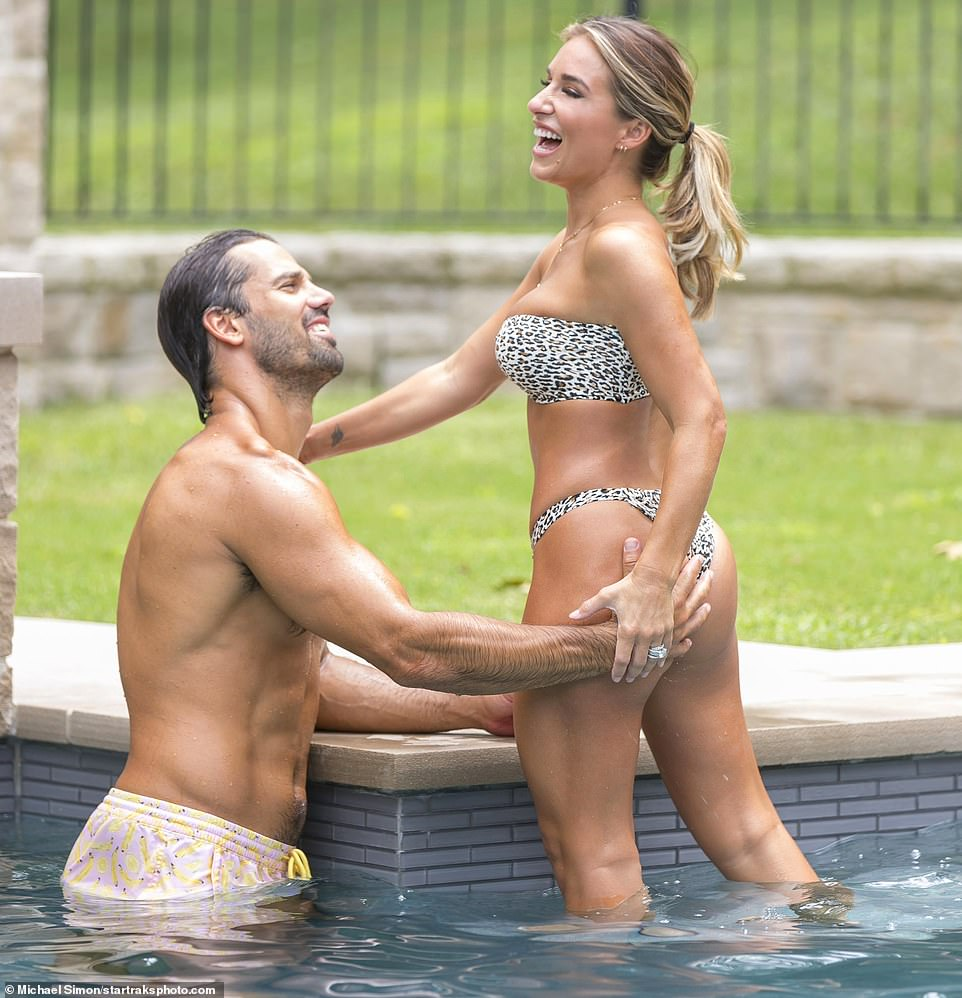 Playful: As the 32-year-old singer-songwriter modeled a racy cheetah-print thong bikini on Wednesday, her man grinned from ear to ear and playfully placed one hand on her pert derrière