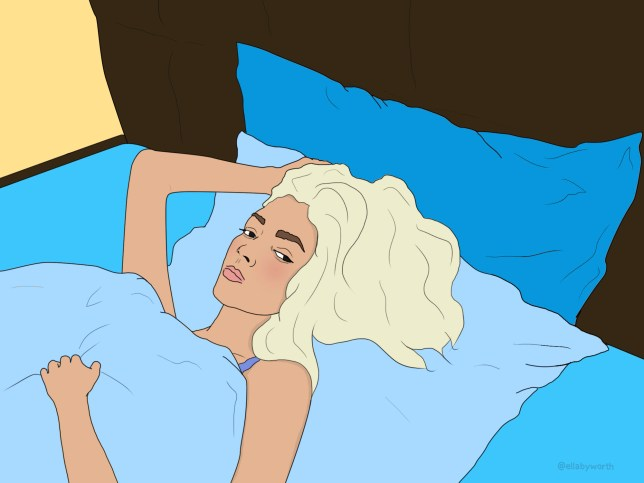 A woman lying in bed looking despondent
