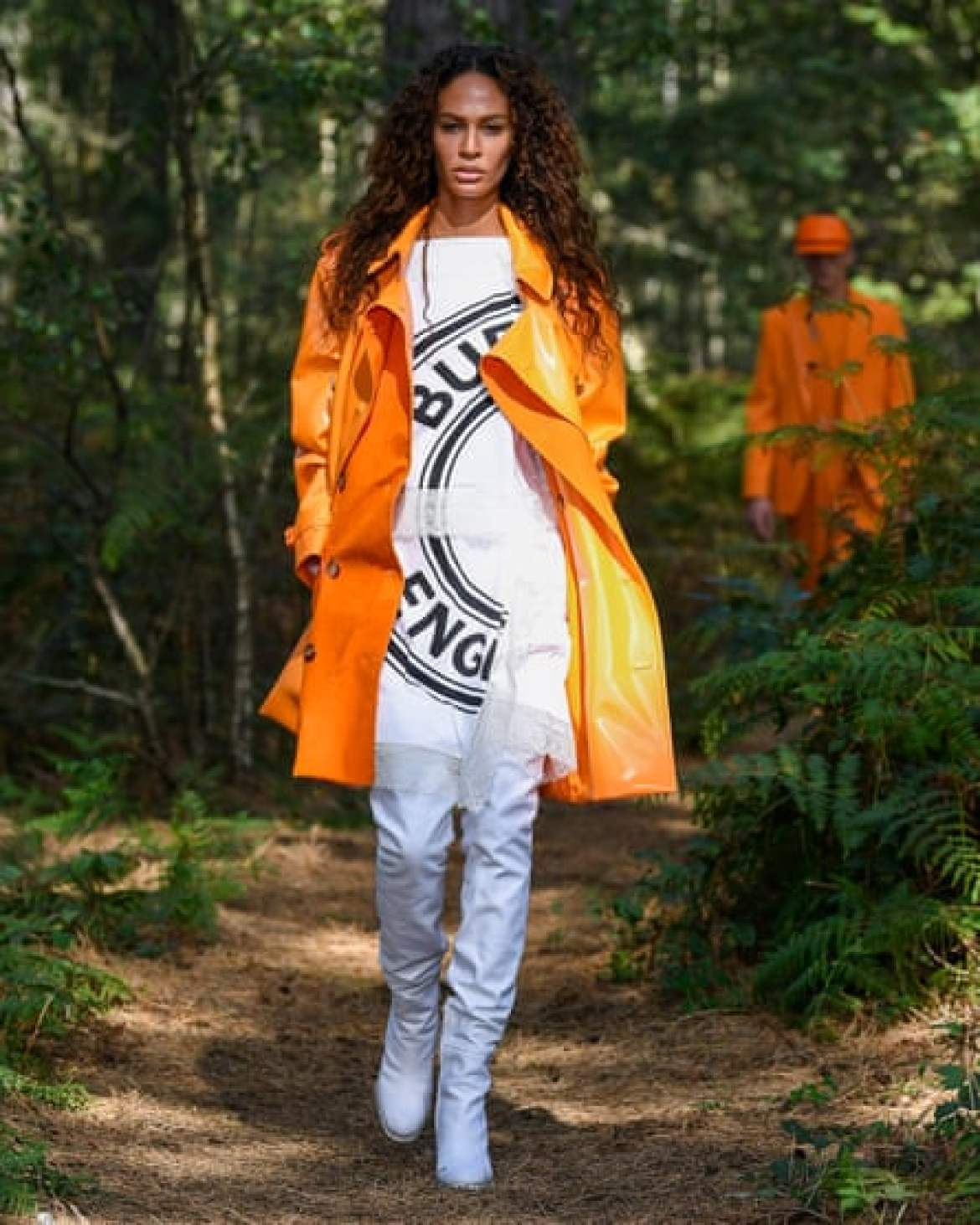 Orange trenchcoat, T-shirt with logo, tight white trousers