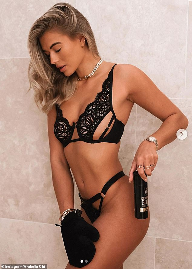 Golden glow:The model, 29, wore a set of black lace underwear as she accessorised with a large gold chain and watch as she applied fake tan to get her 'golden glow'