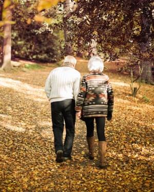 Older couple walking together in park.