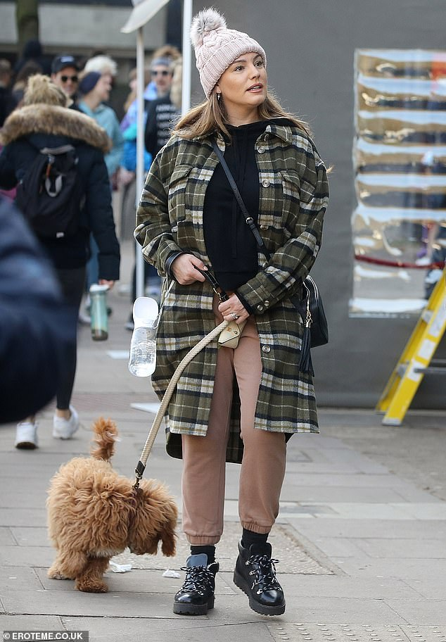 Staying warm: Her iconic curves made her a household name but Kelly Brook covered up her hourglass physique on Saturday in a plaid shirt and brown jogging bottoms