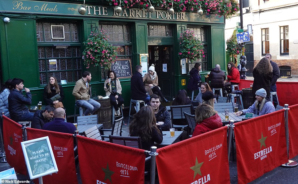 People enjoy afternoon drinks at Borough Market in London before pubs close tonight