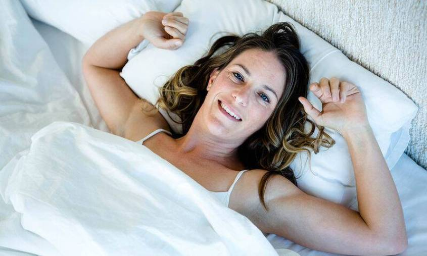 bigstock-smiling-woman-waking-up-in-he-121770425