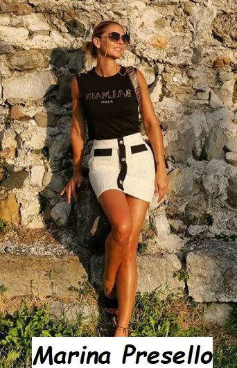 Giornalista Marina Presello che sorride davanti a un muretto
