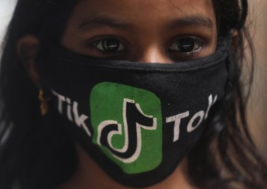 A young woman wears a mask with the TikTok logo in a slum in Mumbai (Reuters)