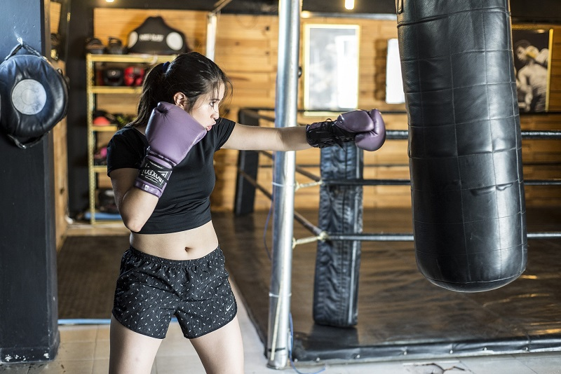 Herbalife24 Products Woman Punching a Punching Bag with Purple Boxing Gloves On