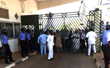 See the Members of House of Representative scaling through the gate to the national Assembly during the teargas attack in Abuja.
