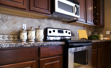 new uses kitchen with dark brown cabinetry stainless steel appliances neutral backsplash tile and cream color canisters on multicolor countertop new uses