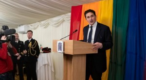 A photo of United Kingdom Defense Minister Johnny Mercer speaking at a podium with a rainbow flag backdrop behind him.