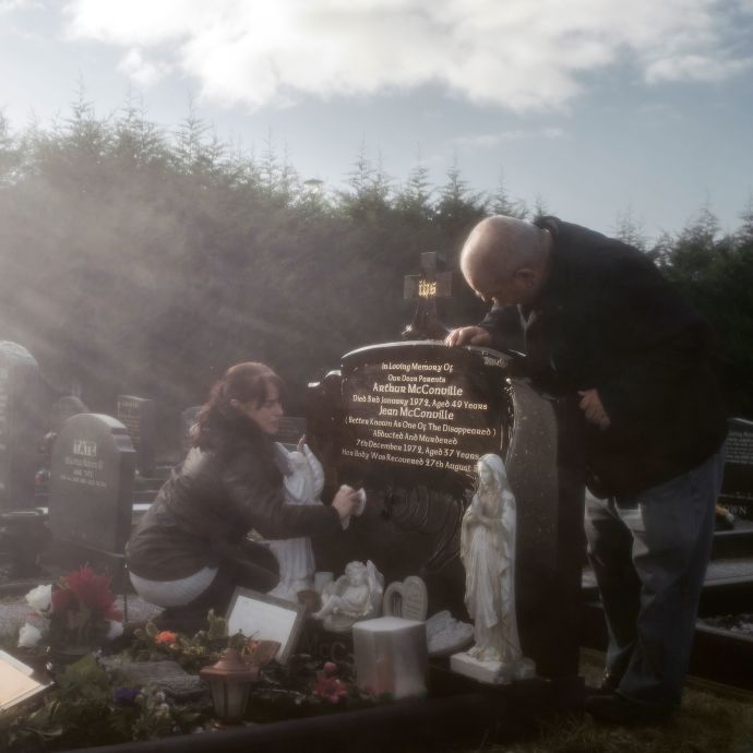 Archie and Susan McConville tending to Jean McConville's grave, at Holy Trinity Cemetery, outside Belfast.