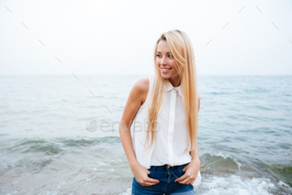 Cheerful woman with long blonde hair standing on the beach