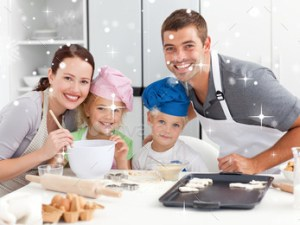 Portrait-of-a-joyful-family-cooking-littles-cakes-against-snow-falling-2018-Stock-Photo