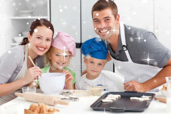 Portrait of a joyful family cooking littles cakes against snow falling