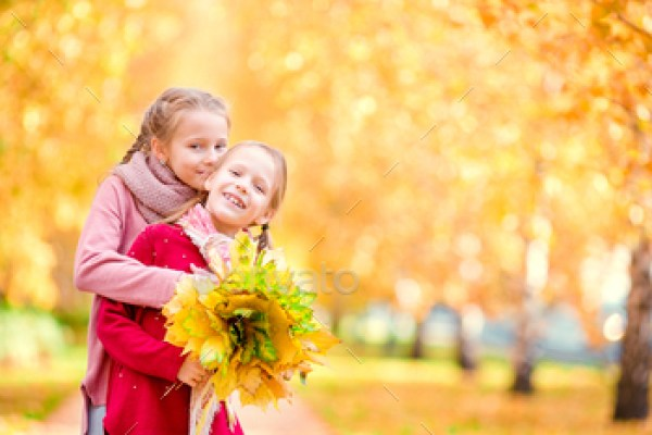 Little happy girl outdoors on a warm autumn day. Kids in fall