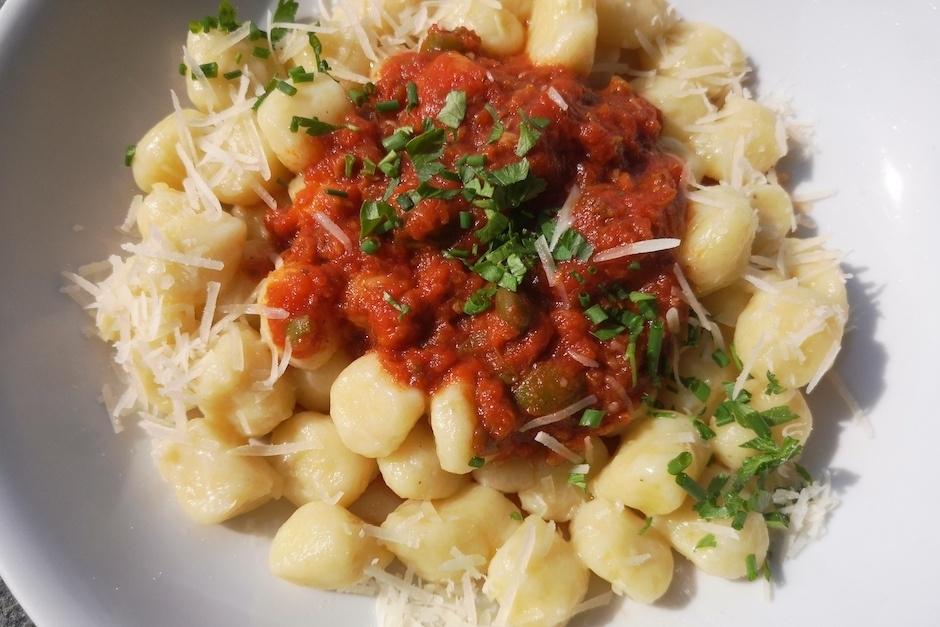 Gnocci mit Tomatensause und Schnittlauf, auf weißem Teller.