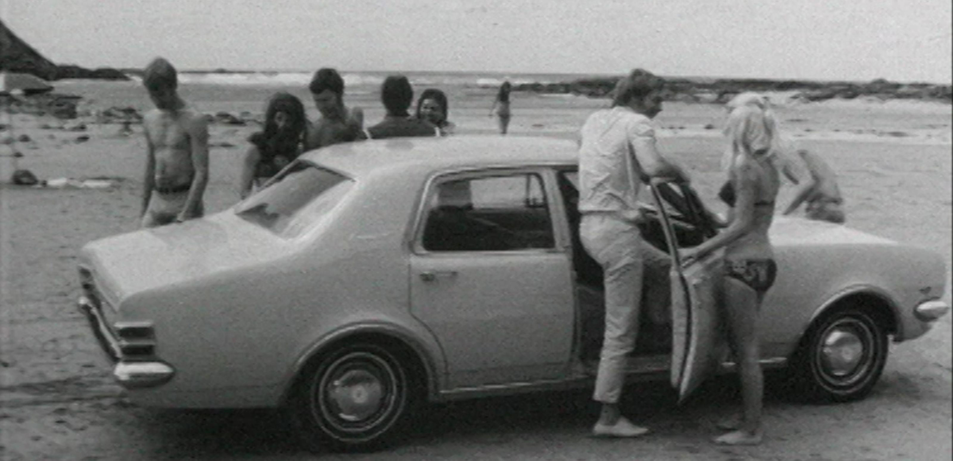 a group of young people stand around a holden car on a beach [ 3200 x 1550 Pixel ]