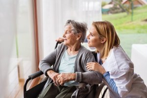 at home care scottsdale caregiver with elderly female gazing out window in wheelchair