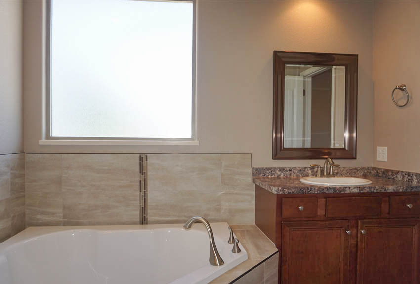 the corner soaking tub has a storage vanity at each end.