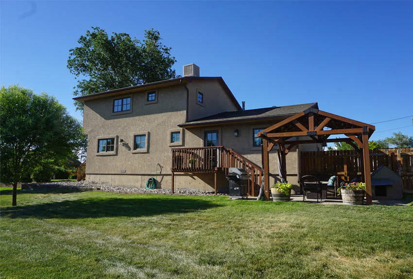 The back of 2575 Young Court has a deck & concrete patio with a pergola