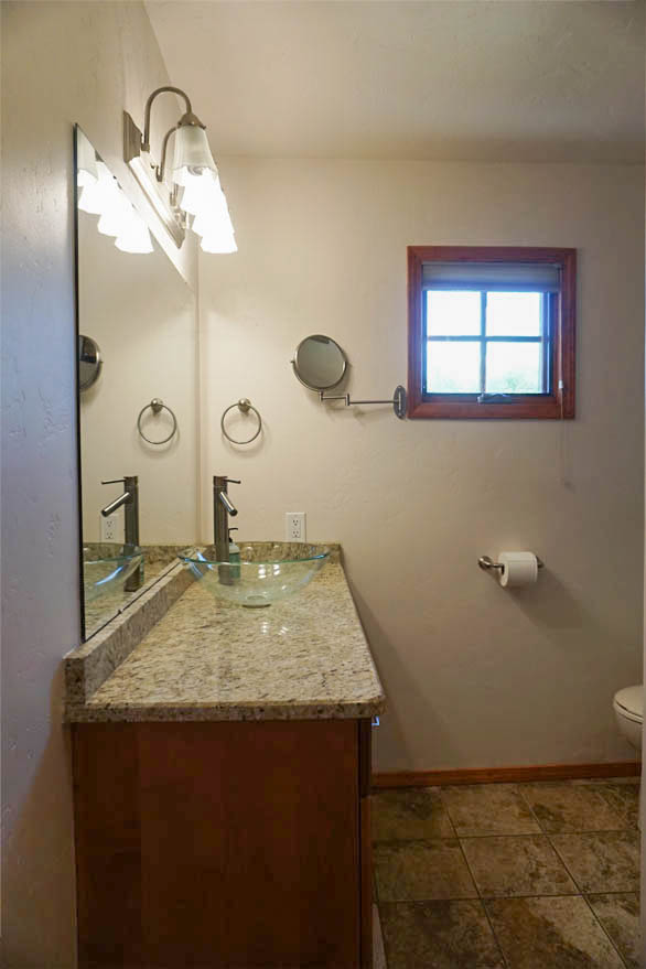 Hall Bath is downstairs, and has a tiled shower, storage vanity with vessel sink & toilet