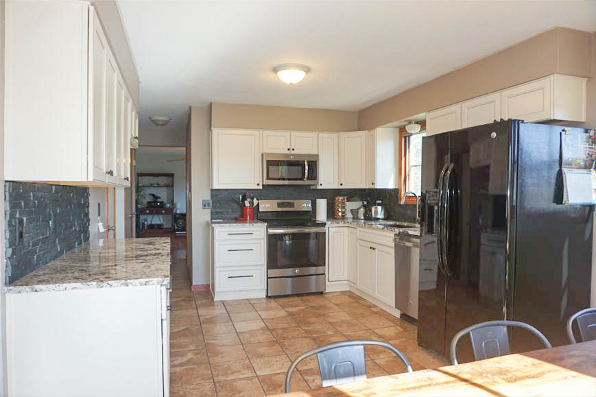 Kitchen has granite counters, tiled back splash, and white cabinets