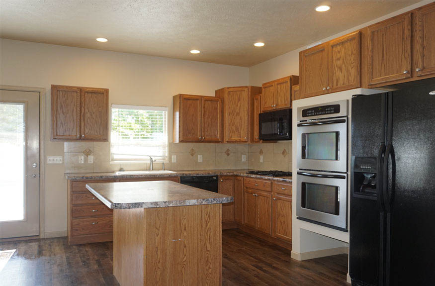 Kitchen includes an island, and all appliances - including double wall ovens and a gas cooktop.