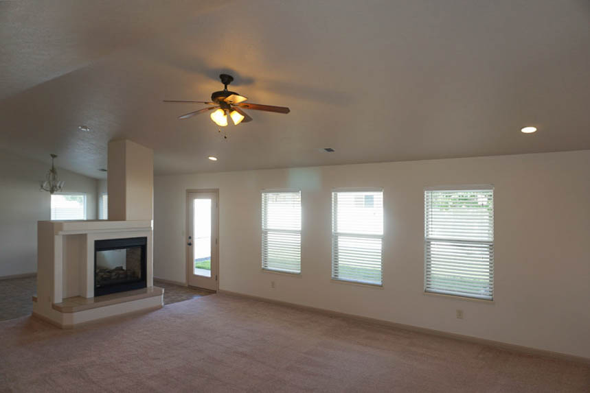 The living room of 199 Winter Hawk has windows overlooking the back patio to let in natural light, a double sided fireplace, and a lighted ceiling fan.
