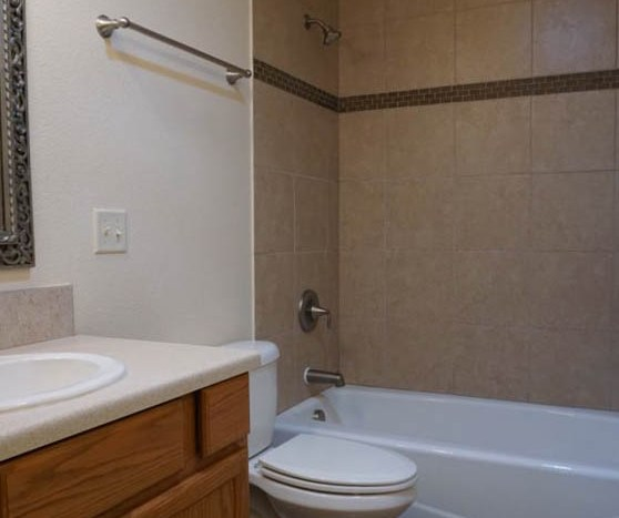 The upstairs full bathroom has two storage vanities, an in-tub shower, and toilet.