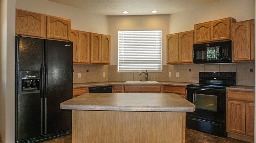 The kitchen of 2995 Golden Hawk has a storage island with seating, all appliances, and a walk-in pantry.