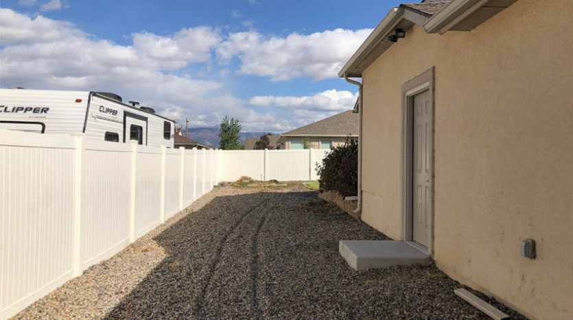 The RV parking area of 164 Winter Hawk runs along the north end of the property.