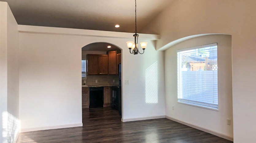 The dining room has a large picture window, chandelier, and decorating shelf above the wall separating the dining from the kitchen.